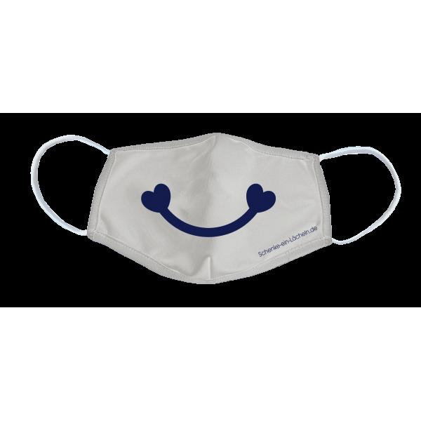 """Das Bild zeigt die """"Schenke ein Lächeln"""" Alltagsmaske in weiß mit aufgedrucktem Lächeln in blau."""