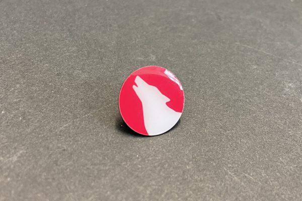Das Bild zeigt einen Ansteckpin mit Wolfskopf in Candy