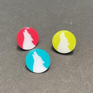 Das Bild zeigt ein 3er-Set Ansteckpins mit dem Wolfskopf in den drei Farben Candy, Petrol und Lemon.